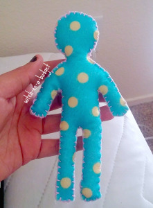[Visual Description: A blue poppet with yellow polka dots and light pink embroidery around the edges.]