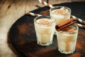 Traditional winter eggnog  with milk, rum and cinnamon, sprinkle